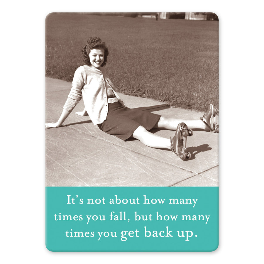 "A rectangular magnet with a photo of a woman in roller skates sitting on a sidewalk  and a teal bar at the bottom with the words ""It's not about how many times you fall, but how many times you get back up."" on it."