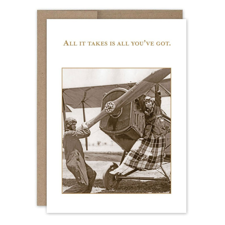 "A woman and a man dressed as pilots attempting to spin the front blade of an old one-person plane. With the text ""All it takes is all you've got."""