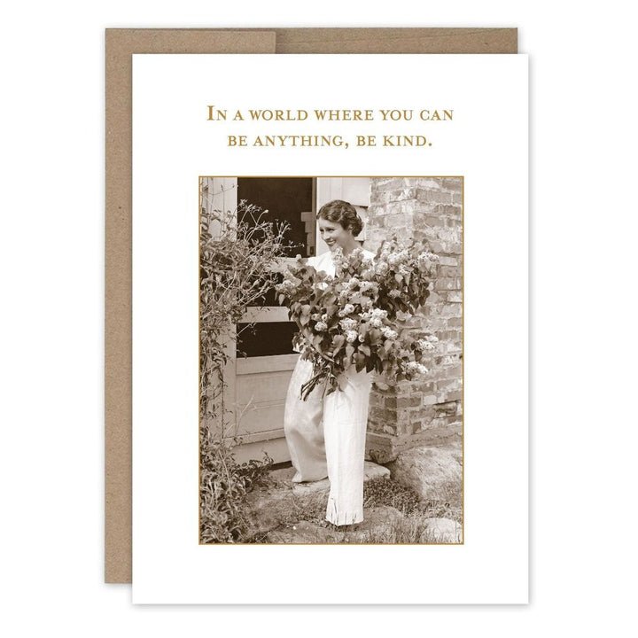 "A woman with a large smile standing out front of a house holding a very large bouquet of wild flowers. With the text ""In a world where you can be anything, be kind."""
