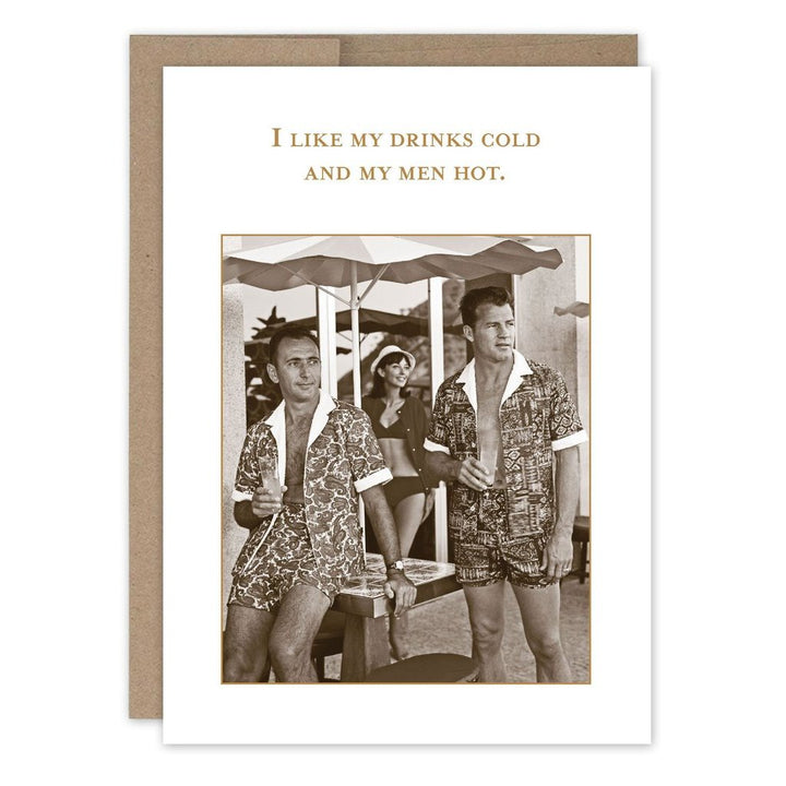"Two men standing under a patio umbrella in matching short shorts and open button-ups stand looking off to their left, both with a drink in their hand. With the text ""I like my drinks cold and my men hot."""