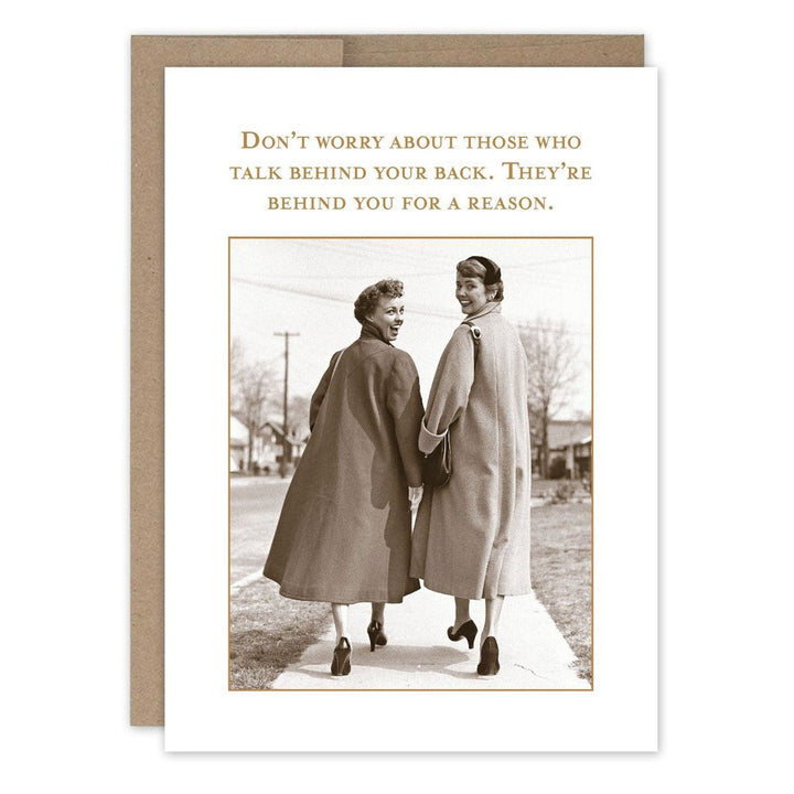 "Two women in long coats and heels walking away down the sidewalk, looking back and smiling at the camera. With the text ""Don't worry about those who talk behind your back. They're behind you for a reason."""
