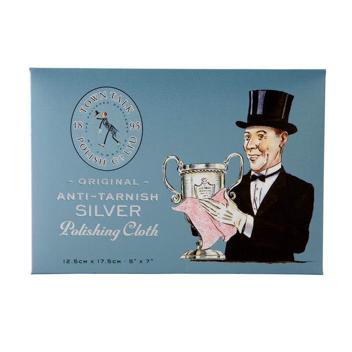 "A rectangular grey card stock envelope with a man dressed in a tux and hat on it. The man is polishing a trophy with a pink cloth. Beside him are the words ""Original anti-tarnish silver polishing cloth"" and the size of the cloth inside the package."