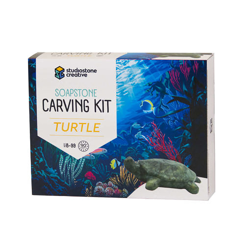 The front of a box with an illustrated ocean scape and a soapstone carving of a turtle on it.