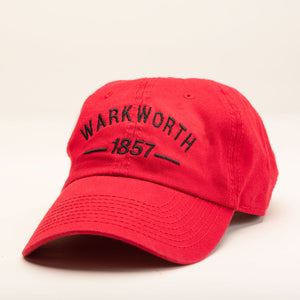 "A red ballcap with ""Warkworth 1857"" stitched in black on the front."