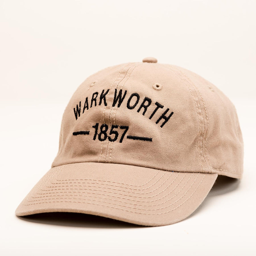 "A tan ballcap with ""Warkworth 1857"" stitched in black on the front."