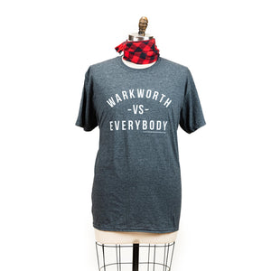 "A grey short sleeve shirt with the words ""Warkworth VS Everybody"" printed in white."