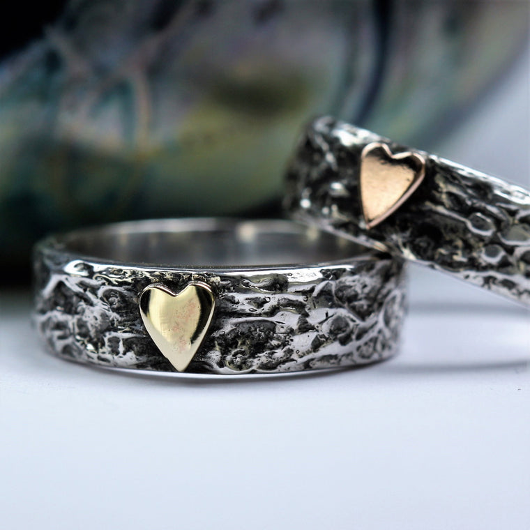 wide silver textured ring featuring a 9ct gold heart and oxidized