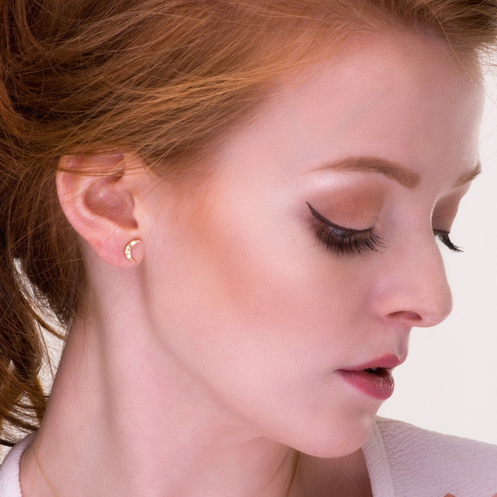 Model wearing the Universe new moon stud earrings in 9ct gold