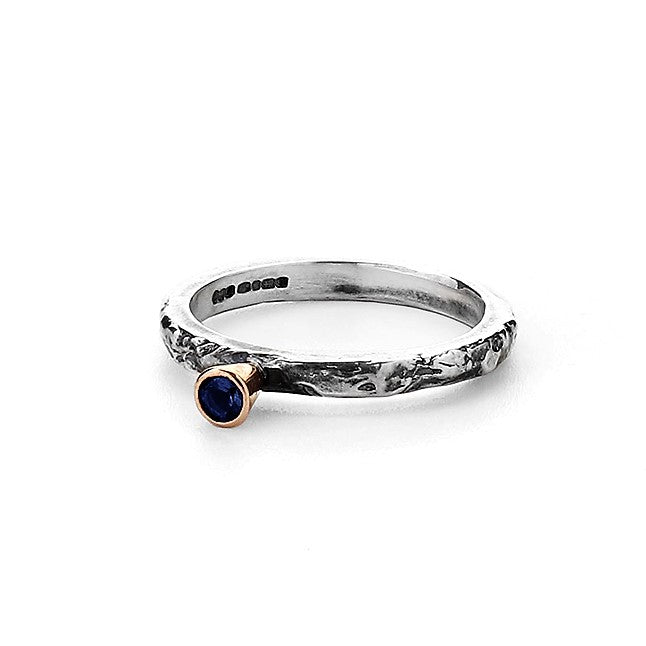 Sapphire Solitaire encased in gold setting on textured ring band