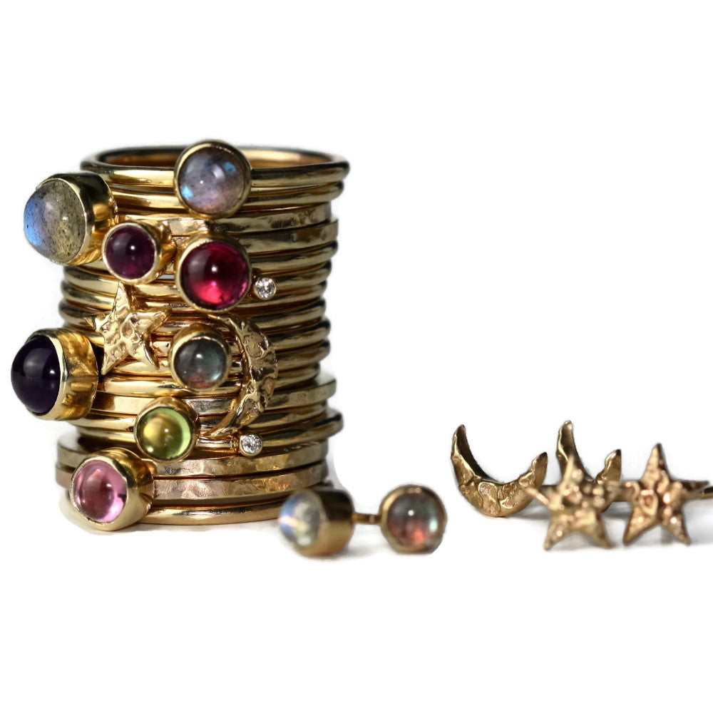 Mixed up stack of solid gold star and moon universe rings and wildflower gemstone rings