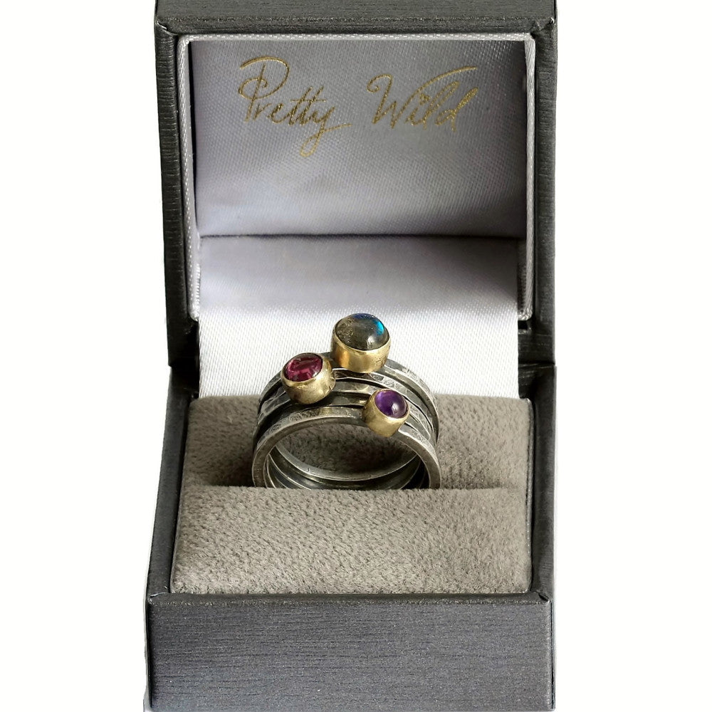 Pretty Wilds branded ring box featuring a full stack of silver and gold blossom stacking rings