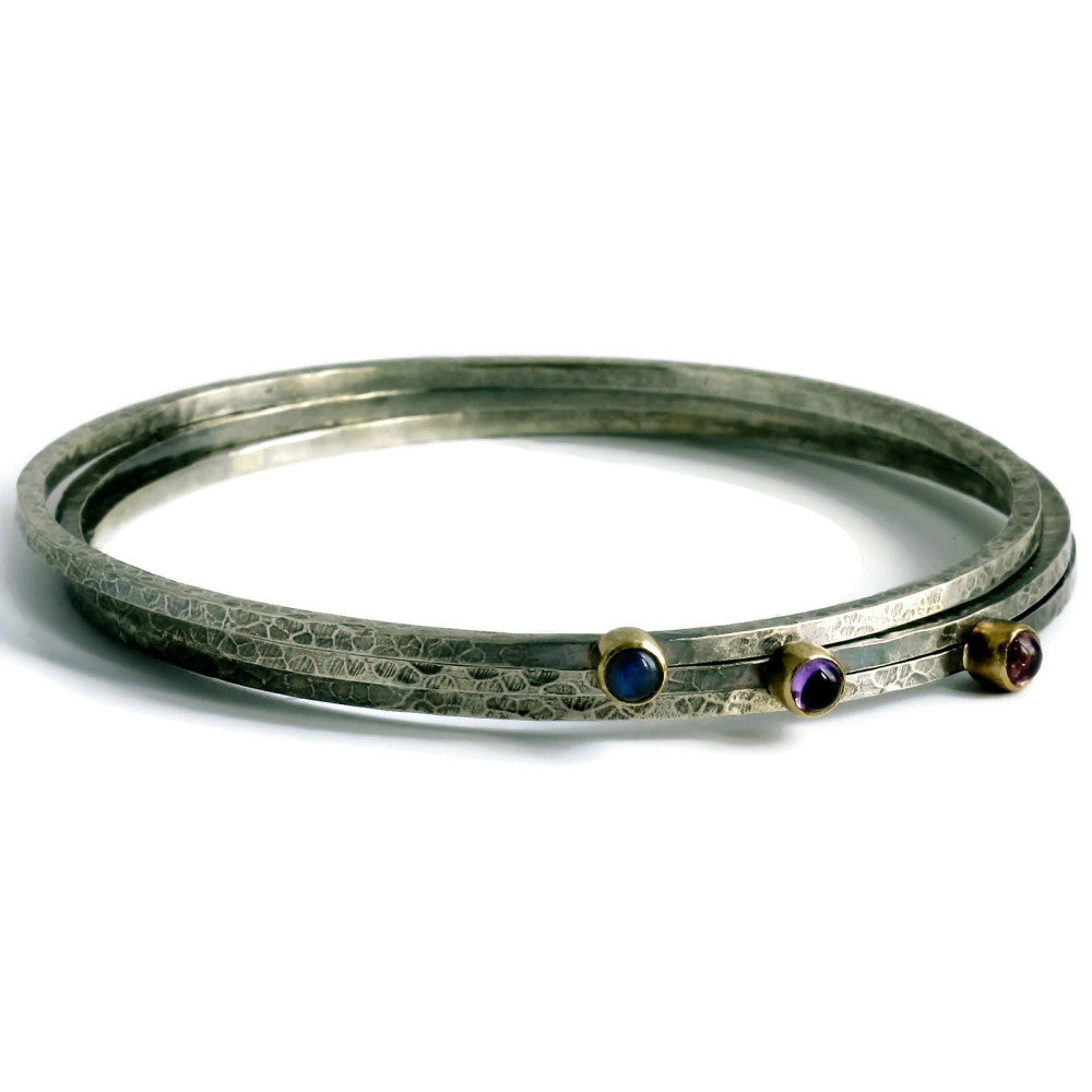 a stack of skinny blossom rustic silver and gold bangles with tourmaline, amethyst and labradorite