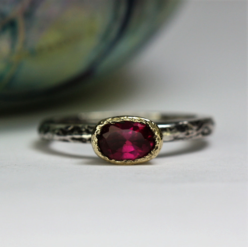 Oval Tourmaline encased in a 9ct gold setting oxidized ring band