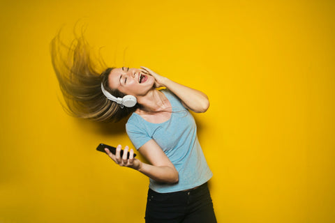 A girl with blonde hair is wearing earphones. She is dancing to the music and her hair is sweeping in the air. She's standing in front of a yellow background.