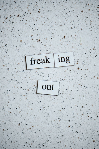 "The words ""freaking out"" are spelled in black letters on white magnets. There is a white background with white speckles"