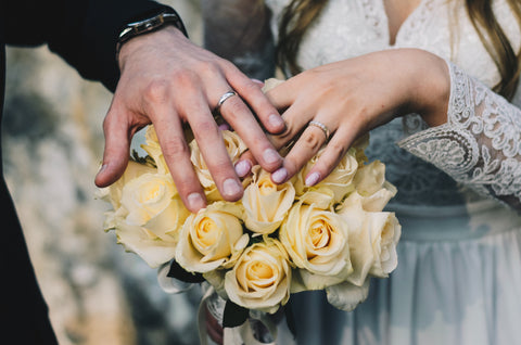 A couple holds hands near a bouquet of yellow roses. They are both wearing wedding rings.