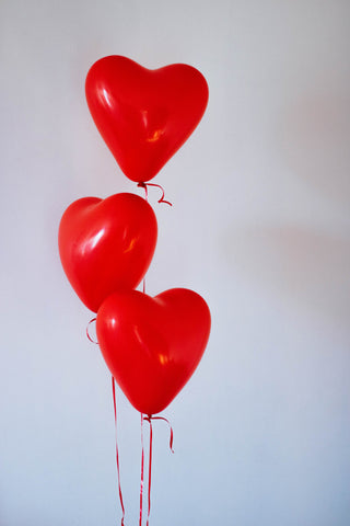 Three red heart-shaped balloons are attached to strings. They are floating in the air with a white background