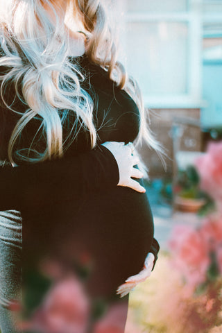 A woman with blonde hair and a black dress has her hands cradled around her pregnant belly.