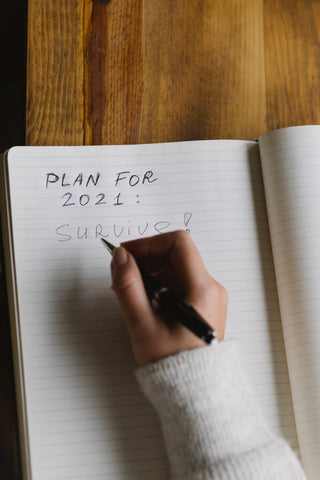 """A close-up of a girl writing in a notebook. She has a pen in her hand and wrote: """"Plan for 2021: Survive!"""""""