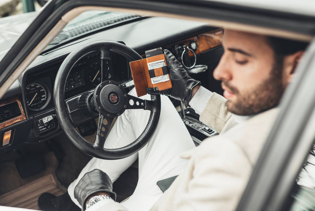 This image features a man holding an Ekster Vachetta Collection smart wallet in his right hand, whilst he sits in the driver's seat of an old vintage car. The Ekster wallet is Brescia Bronze.