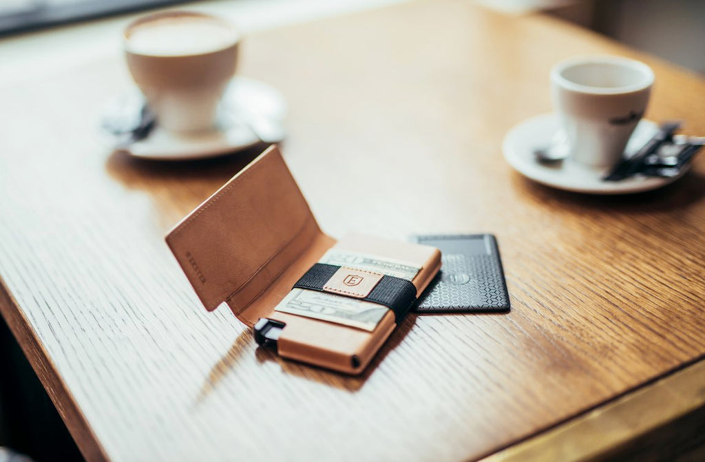 An Ekster trackable wallet and an Ekster tracker card with gps are placed on a coffee table, with coffee cups on the background. The Ekster smart wallet has a 20 dollar bill in it and is placed partly on top of the gps Ekster tracker.