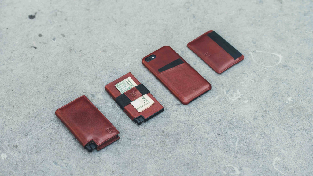 Four Ekster products showcased against a grey concrete background. From left to right; a slim wallet, a simple wallet with a cash strap, an iPhone in an Ekster case, and a minimalist cardholder.
