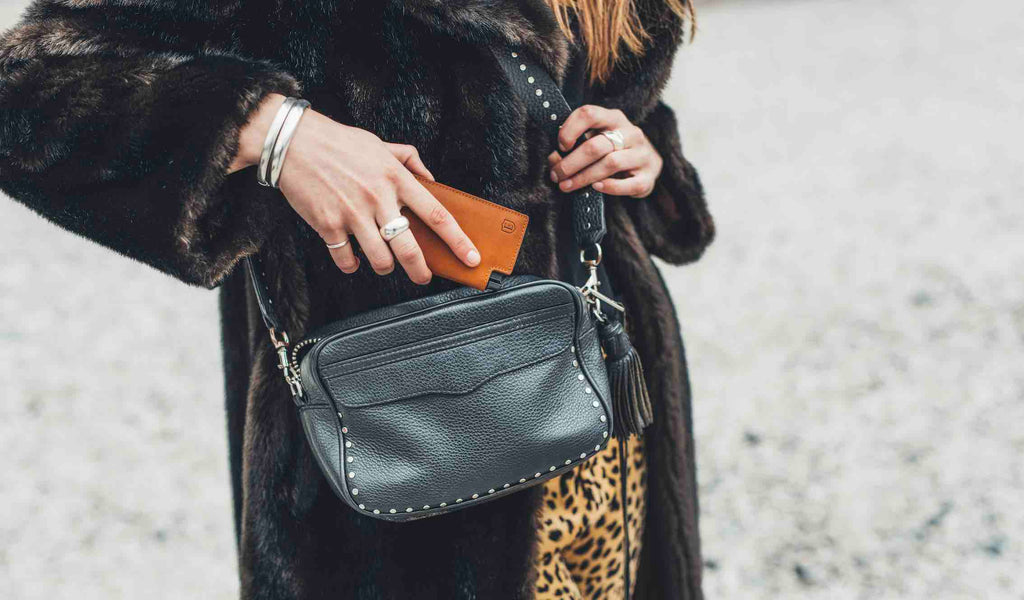 The image shows a woman dressed in a large faux fur coat, holding a black leather bag. She is sliding her Ekster Vachetta Parliament in Brescia Bronze into her wallet.
