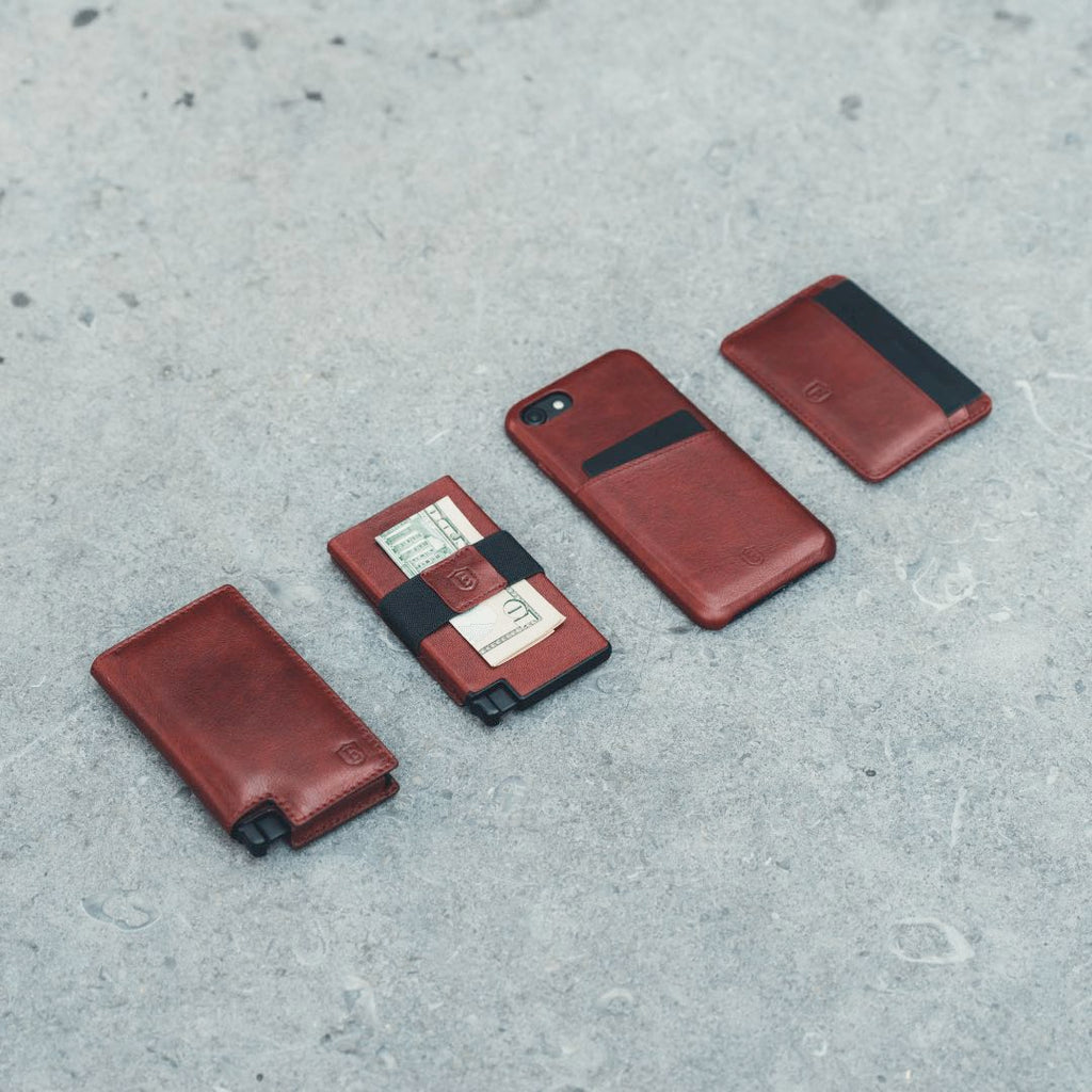 Four Ekster products are presented against a grey concrete background. These are the Ekster Parliament Wallet, the Ekster Senate Cardholder, the Ekster iPhone Case, and the Ekster Secretary Cardholder. They are all in Merlot Red. This pictures showcases the Ekster smart wallets and slim wallets collection.