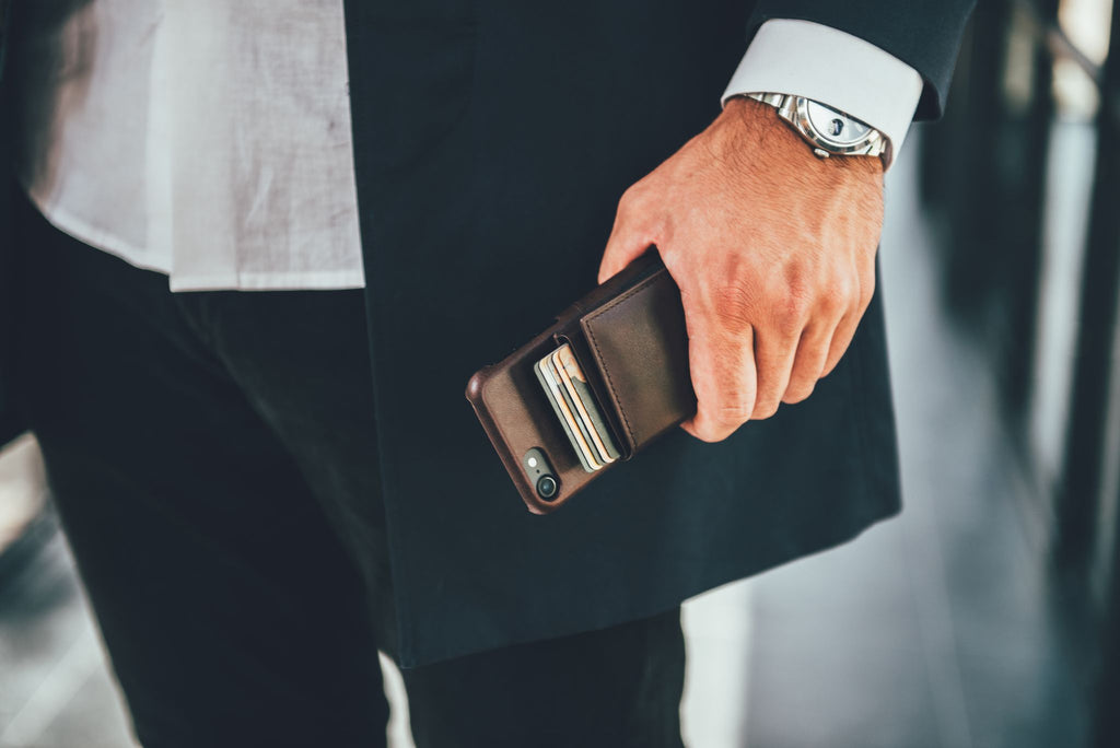 Man in a suit holding a wallet