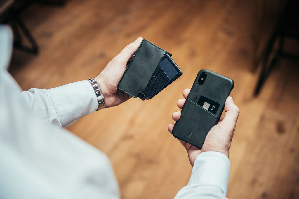 Man holding his phone and a card wallet