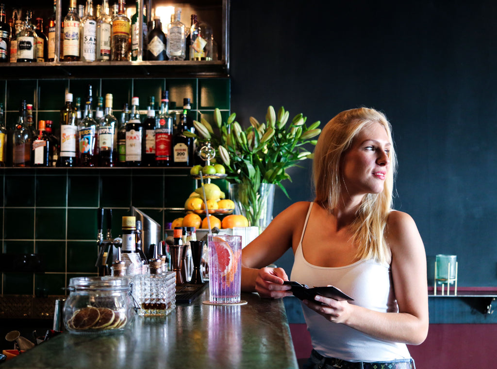 A woman at a bar with her phone wallet and phone