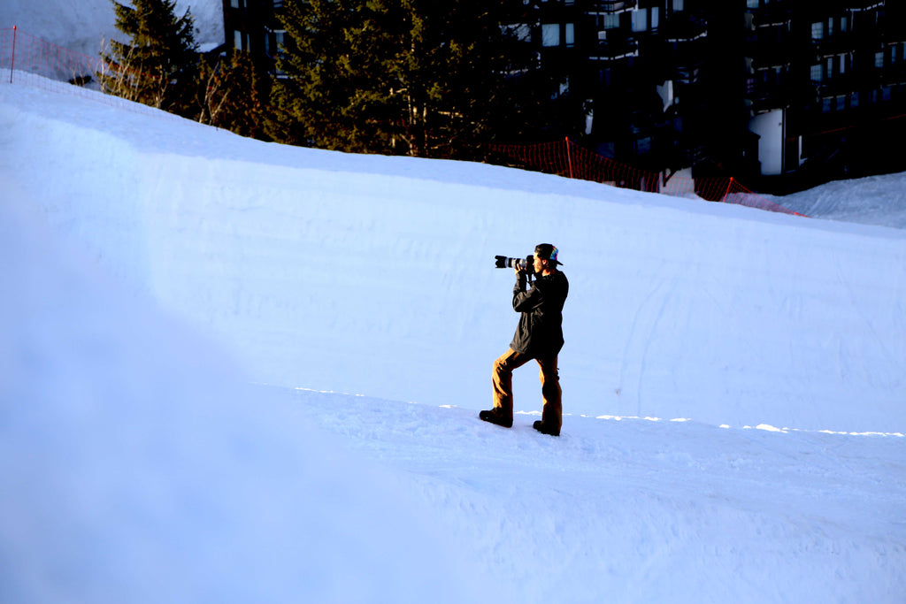 An image of a cameraman shooting amongst the slopes.
