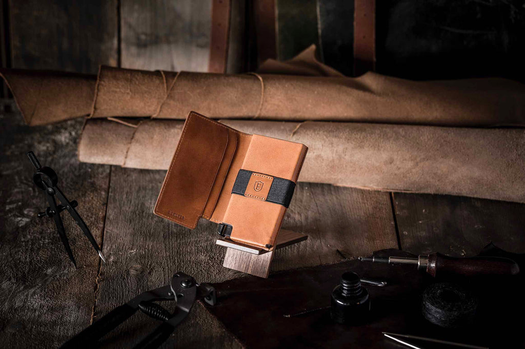 This image features an Ekster wallet in Brescia Bronze, which is a limited edition release called the Vachetta Collection. The wallet is the centre of this picture, against a background of leather and wood.