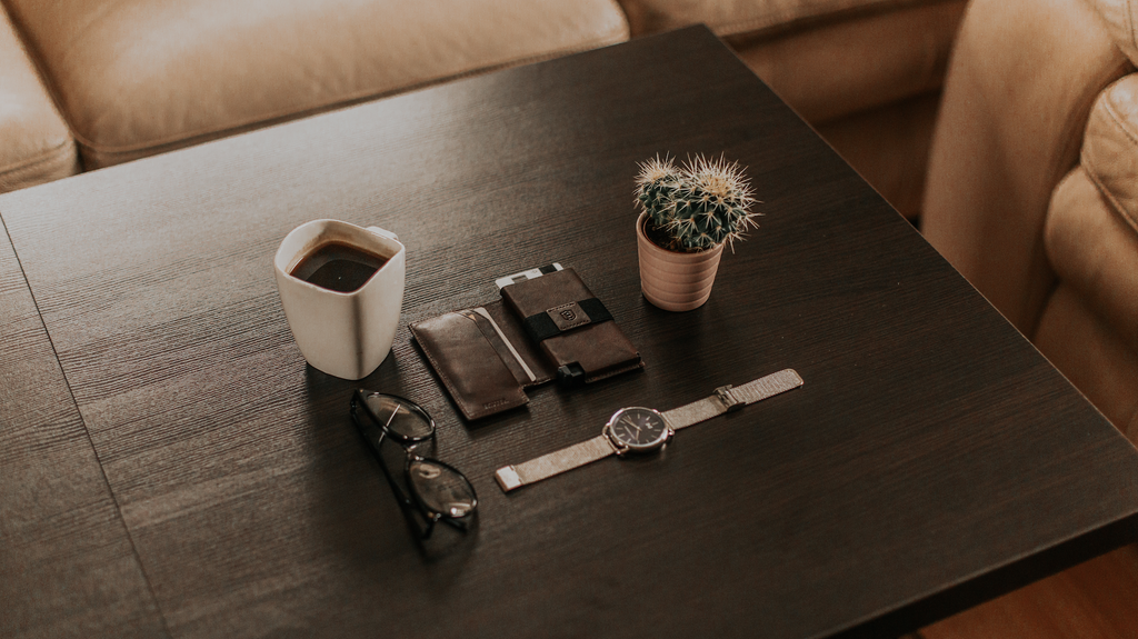 Background is a dark wood table with a few items neatly arranged in the center. The items are an Ekster trackable smart wallet, a watch, a plant, a mug of coffee, and a pair of sunglasses.