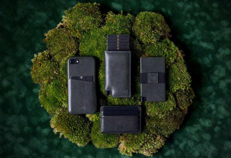 Four Ekster products are placed against a stylized green mossy background. These products are the Ekster iPhone Case, the Ekster 3.0 Parliament Wallet, the Ekster 3.0 Senate Cardholder, the Ekster 3.0 Secretary. These are all Juniper Green. This showcases the Ekster 3.0 products.