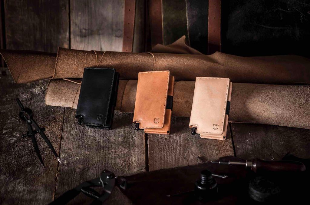 Three Vachetta leather wallets are placed against a background of wood and rolled up Italian leather. From right to left, the Ekster smart wallets are Bologna Black (in black), the Brescia Bronze (in bronze), and the Torino Tan (in tan).