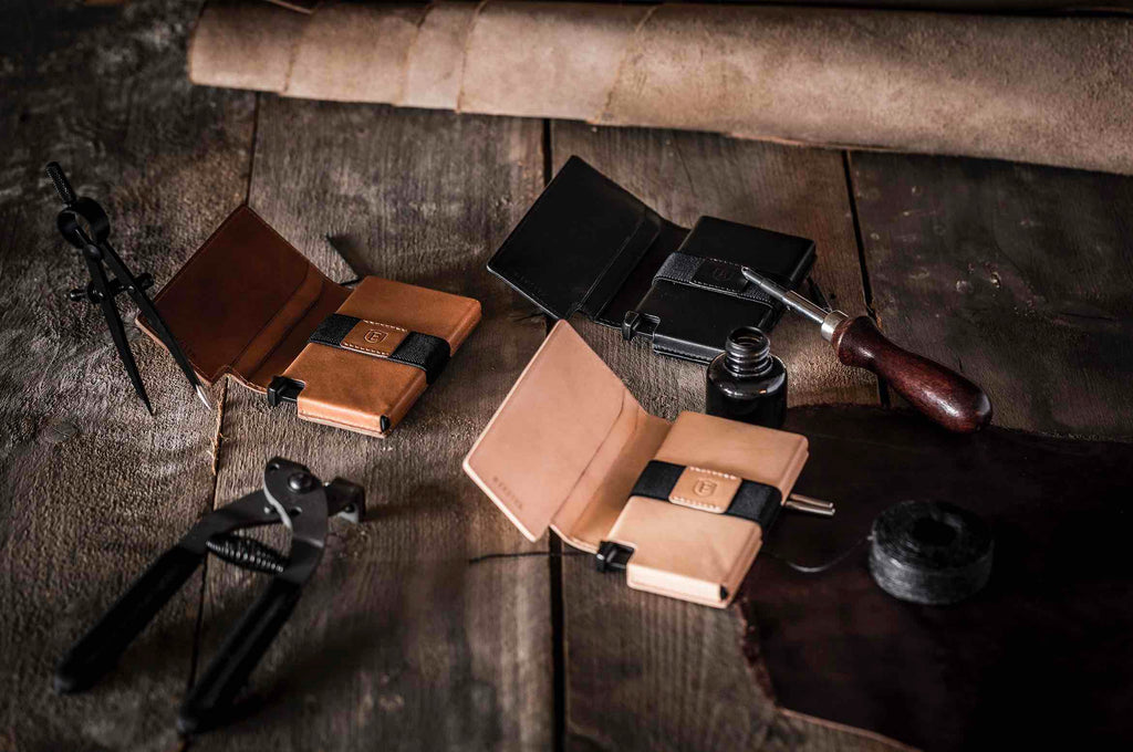 This image features three Ekster smart wallets from the limited edition Vachetta collection. The wallets are placed on a wood and leather background. They are three different finishes; the Bologna Black, the Brescia Bronze, and the Torino Tan.