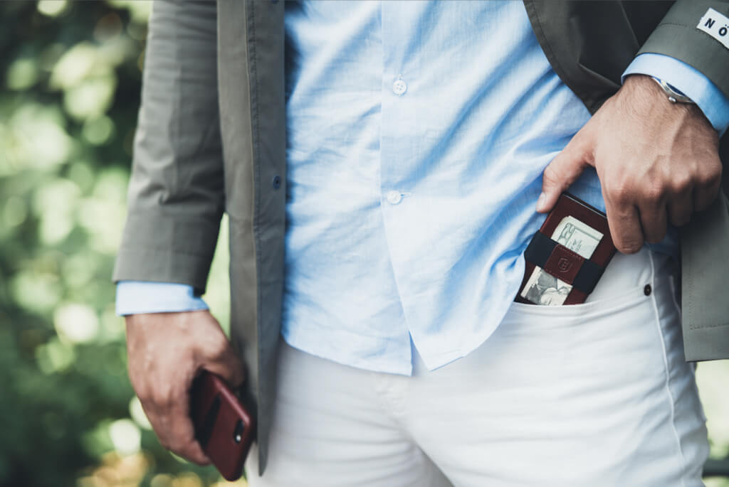 Image of a man sliding an Ekster smart wallet into his pocket. His other pocket holds an iPhone with an Ekster case.
