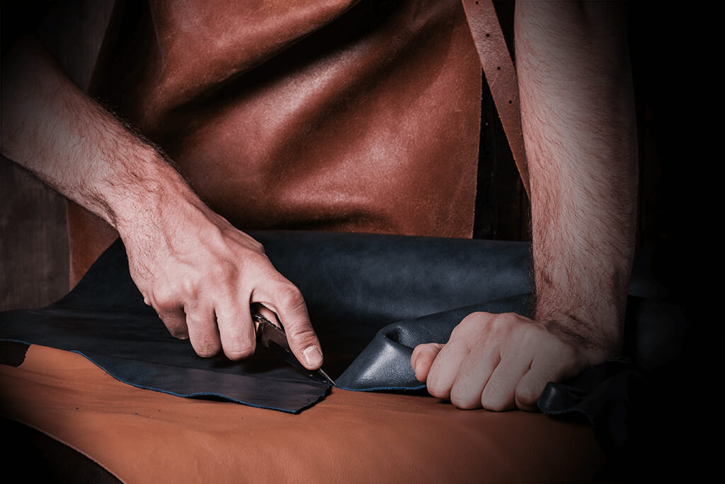 A man's hands use a tool to cut leather in order to make a luxury handmade leather wallet.