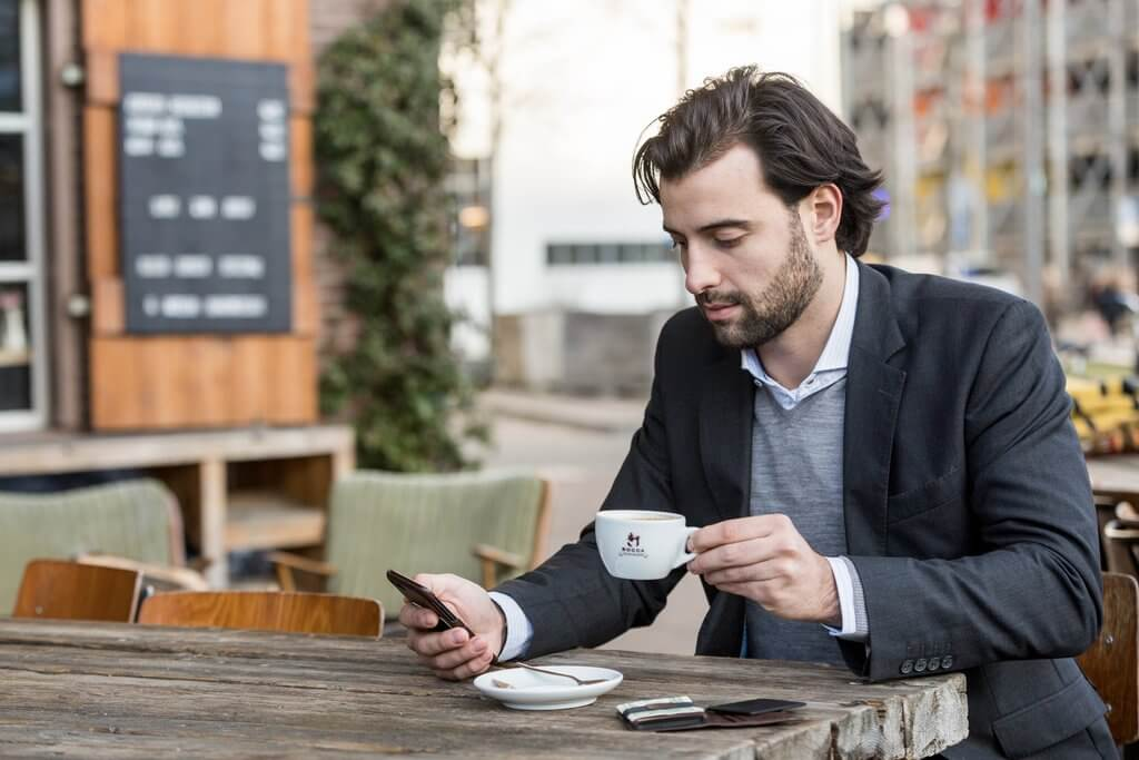 Image of a man in business attire drinking coffee, as he checks his iPhone. There is a travel security wallet on the table in front of him.