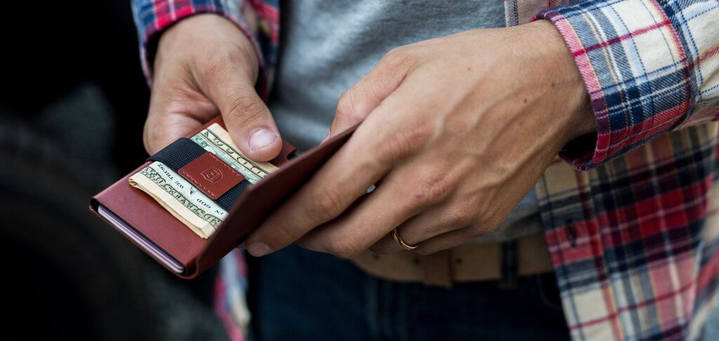 Image of an Ekster smart wallet with a cash strap in a man's hands.