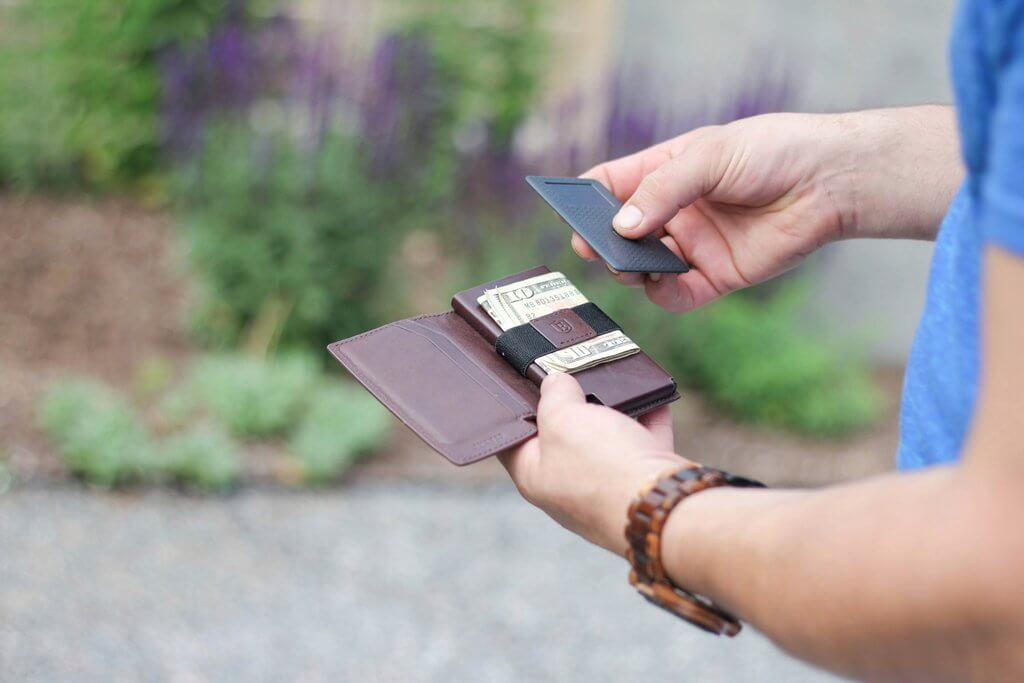 image of a man holding a handmade men's leather wallet and a wallet tracker.
