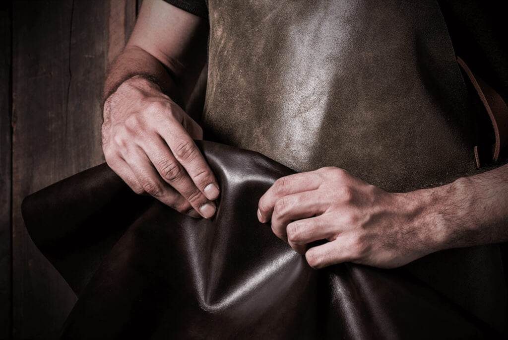 Image of a leather worker's hands, holding uncut leather