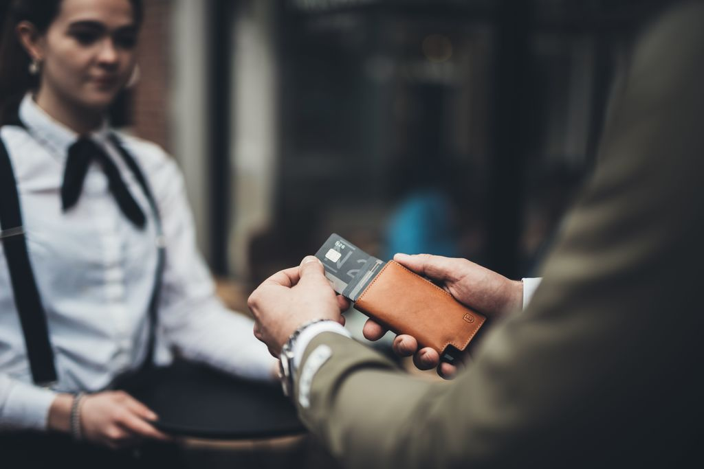 A man taking a card out of his wallet to pay for food