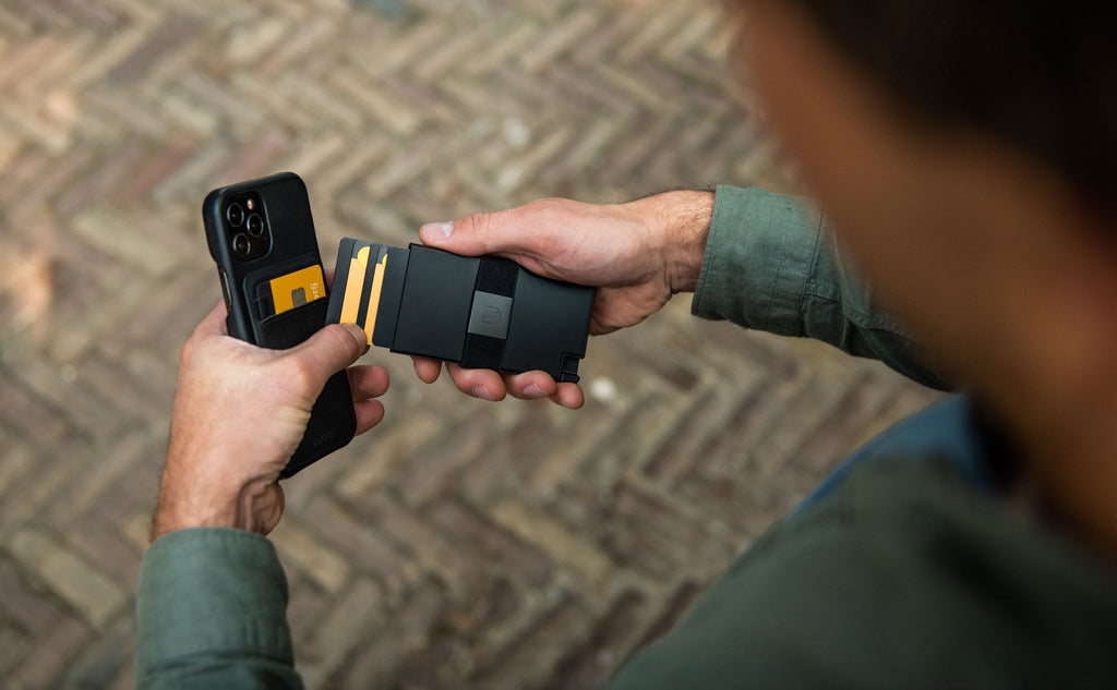 A man holding his phone while attaching a card holder