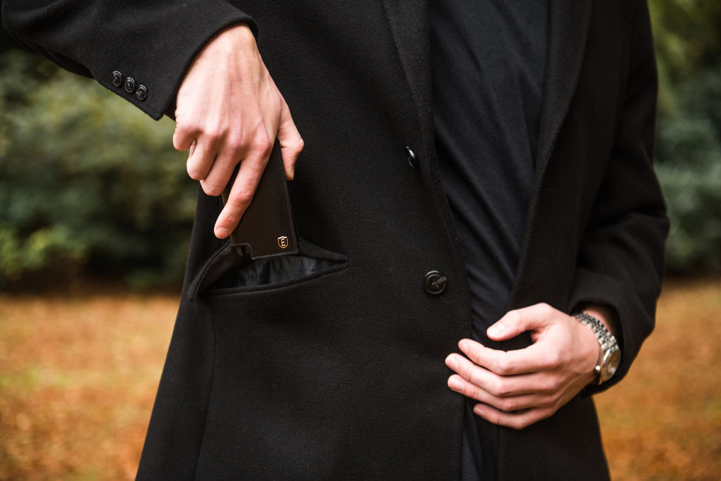 Person putting a card wallet into their coat pocket