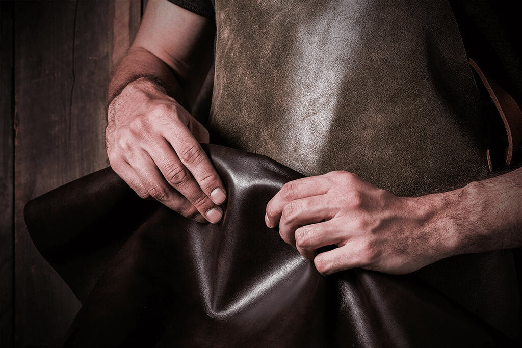 Image of a man holding a leather hide, soon to be made into a handcrafted wallet.
