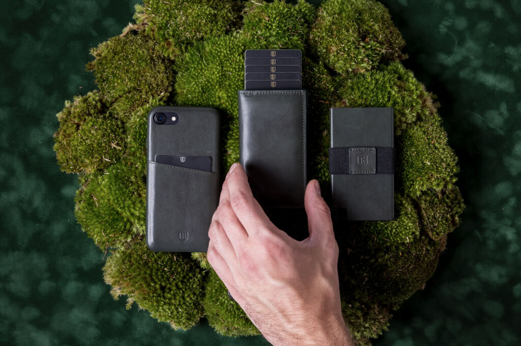 Image of an Ekster iPhone case, and two trendy wallets, side-by-side. A hand reaches for the wallet in the middle, which showcases the card eject function.