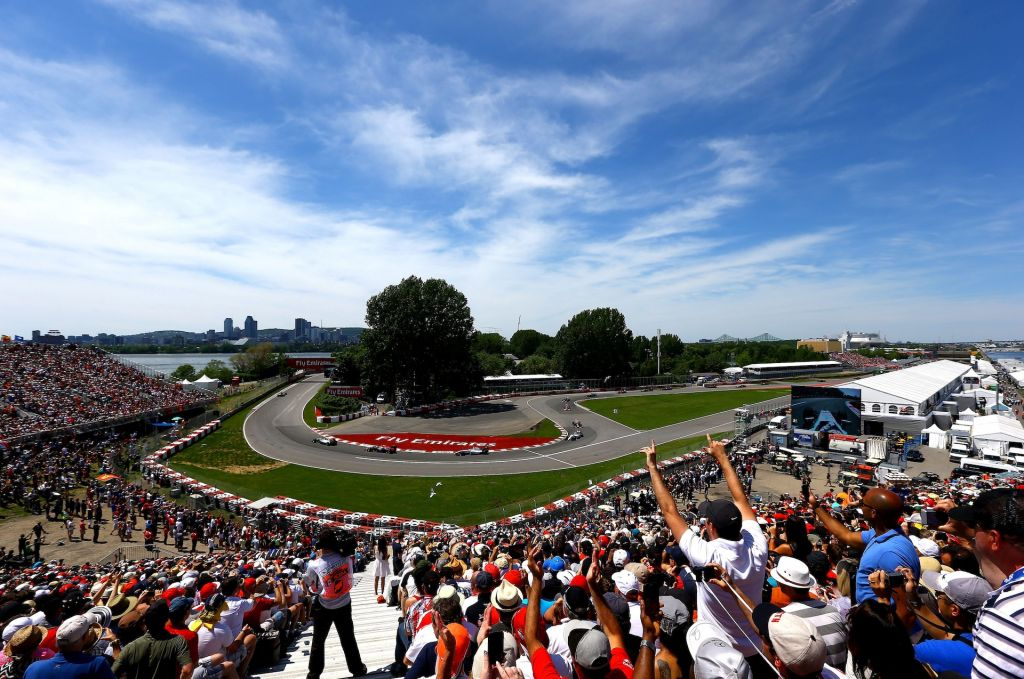 Cheering crowd as F1 cars race through the turn