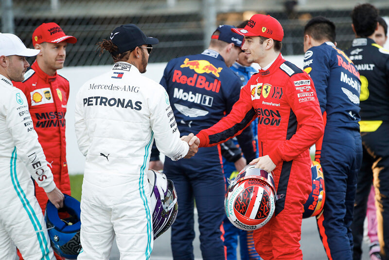 F1 drivers Hamilton and LeClerc shake hands.